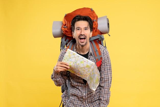 Widok z przodu młody mężczyzna idący na wędrówki z plecakiem trzymającym mapę na żółtym tle wycieczka firmowa powietrze natura kampus las kolor