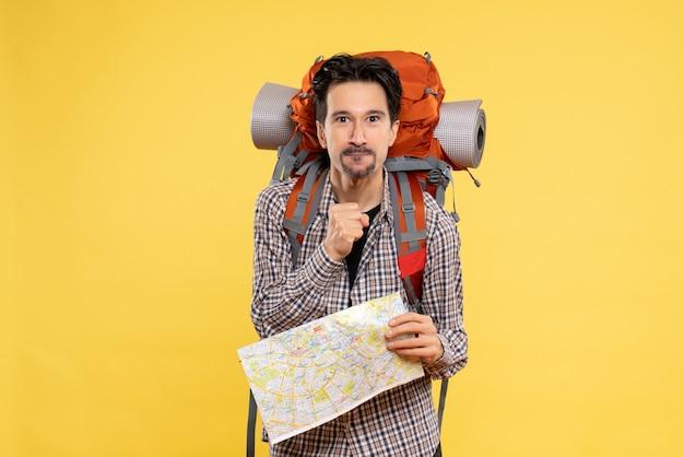 Widok z przodu młody mężczyzna idący na wędrówki z plecakiem trzymającym mapę na żółtym tle wycieczka lotnicza firma przyrodnicza kampus leśny kolor