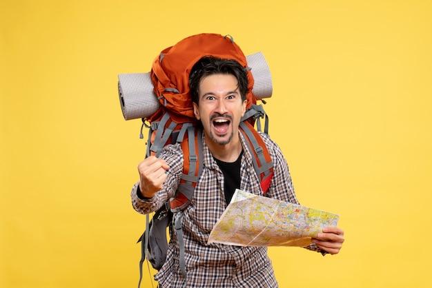 Widok z przodu młody mężczyzna idący na wędrówki z plecakiem trzymającym mapę na żółtym tle wycieczka lotnicza firma przyrodnicza kolor kampusu