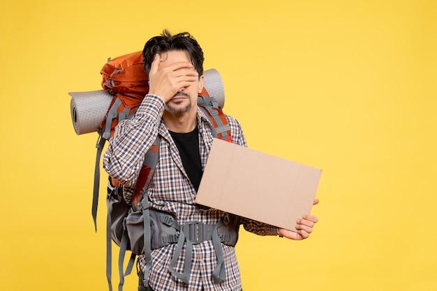 Widok z przodu młody mężczyzna idący w góry z plecakiem na żółtym tle mapa kolor firma wycieczka kampus powietrze las natura