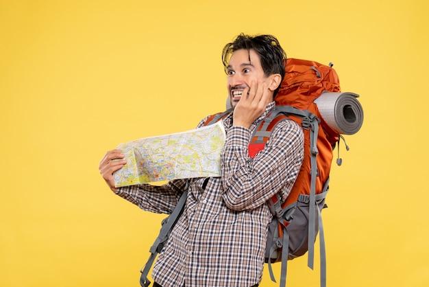 Widok z przodu młody mężczyzna idący w góry z plecakiem obserwujący mapę na żółtym tle firma leśna natura kampus kolor podróż lotnicza