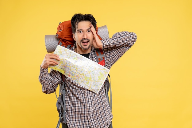 Widok z przodu młody mężczyzna idący w góry z plecakiem obserwujący mapę na żółtym tle wycieczka do towarzystwa leśnego natura kampus powietrze