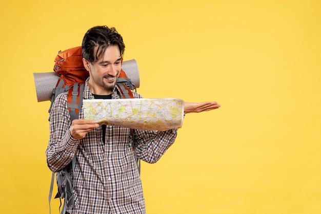 Widok z przodu młody mężczyzna idący w góry z plecakiem obserwujący mapę na żółtym tle wycieczka do towarzystwa leśnego natura kolor powietrze