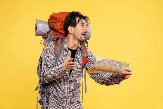 Widok z przodu młody mężczyzna idący w góry z plecakiem obserwujący mapę na żółtym tle wycieczka firmowa przyroda kampus las powietrze