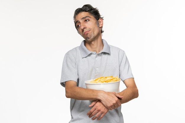Widok z przodu młody mężczyzna jedzący chipsy ziemniaczane podczas oczekiwania na zakończenie filmów na białej powierzchni