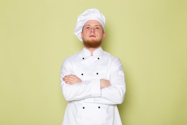 Widok z przodu młody mężczyzna kucharz w białym garniturze gotować biały kapelusz wpr pozowanie