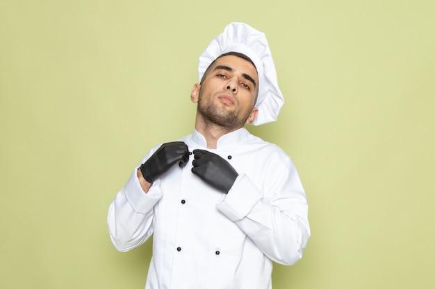 Widok z przodu młody mężczyzna kucharz w białym garniturze kucharza w czarnych rękawiczkach na zielono