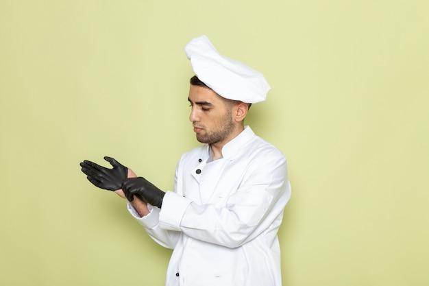 Widok z przodu młody mężczyzna kucharz w białym garniturze na sobie czarne skórzane rękawiczki na zielono