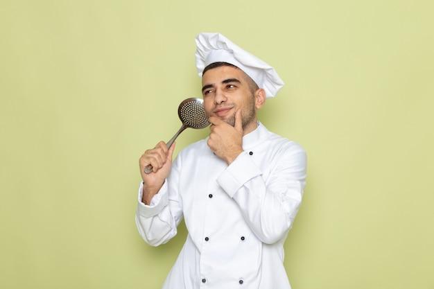 Widok z przodu młody mężczyzna kucharz w białym garniturze, trzymając srebrną łyżkę i myślący na zielono