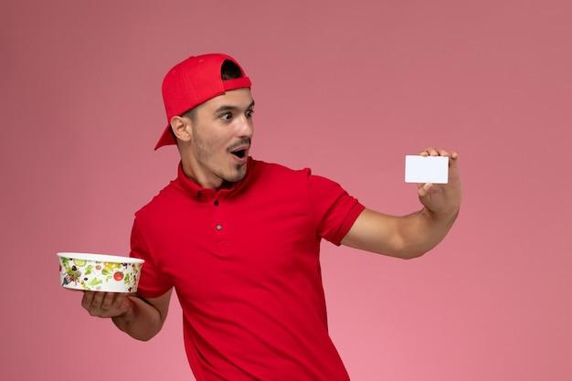 Widok z przodu młody mężczyzna kurier w czerwonej pelerynie mundurowej trzymający białą plastikową kartę i miskę dostawy na jasnoróżowym tle.