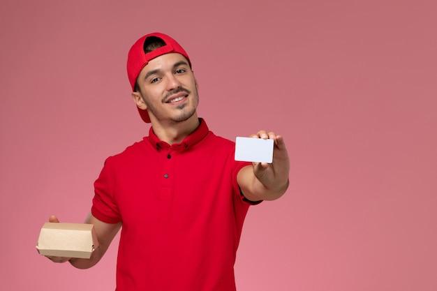 Widok z przodu młody mężczyzna kurier w czerwonej pelerynie mundurowej trzymający małą paczkę z białą kartą na różowym tle.