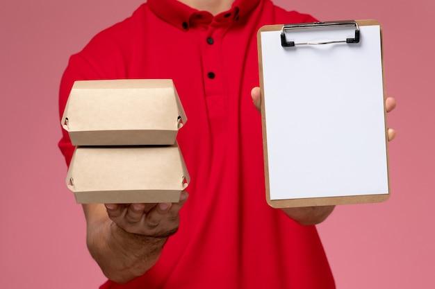 Widok z przodu młody mężczyzna kurier w czerwonej pelerynie mundurze trzyma notatnik i mały pakiet z jedzeniem na różowym tle.