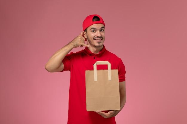 Widok z przodu młody mężczyzna kurier w czerwonej pelerynie mundurze trzymając papierowy pakiet żywności na różowym tle.