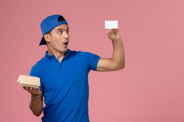 Widok z przodu młody mężczyzna kurier w niebieskiej pelerynie mundurowej trzymający małą paczkę z dostawą żywności i białą kartę na jasnoróżowej ścianie