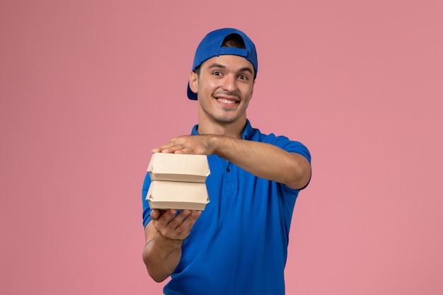 Widok z przodu młody mężczyzna kurier w niebieskiej pelerynie mundurowej trzymający małe opakowania z dostawą żywności na różowej ścianie