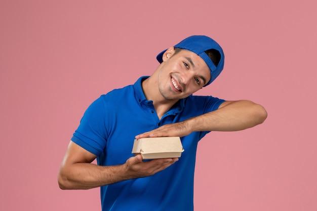 Widok z przodu młody mężczyzna kurier w niebieskiej pelerynie mundurowej trzymający mały pusty pakiet żywności dostawy z uśmiechem na różowej ścianie