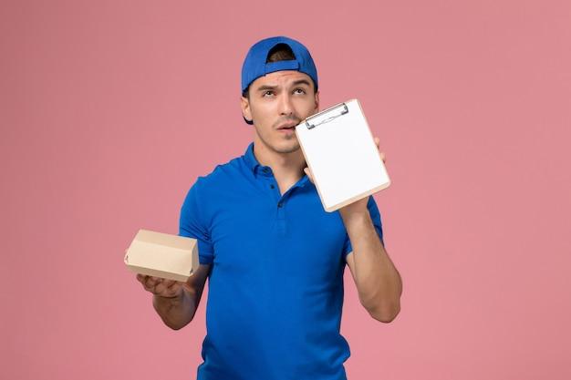 Widok z przodu młody mężczyzna kurier w niebieskiej pelerynie munduru trzymający małą paczkę z dostawą żywności i myślący notatnik na jasnoróżowej ścianie