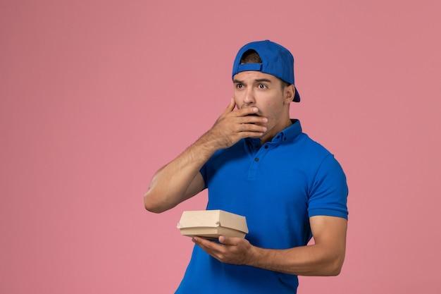 Widok z przodu młody mężczyzna kurier w niebieskiej pelerynie mundurze, trzymając pakiet żywności dostawy z zaskoczonym wyrazem na różowej ścianie