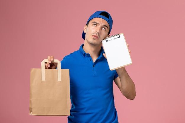 Widok z przodu młody mężczyzna kurier w niebieskim mundurze i pelerynie z pakietem dostawy i notatnikiem na rękach na różowej ścianie