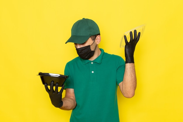 Widok z przodu młody mężczyzna kurier w zielonej koszuli, zielona czapka otwierająca miskę z jedzeniem w czarnej masce na żółtym tle świadcząca usługę koloru