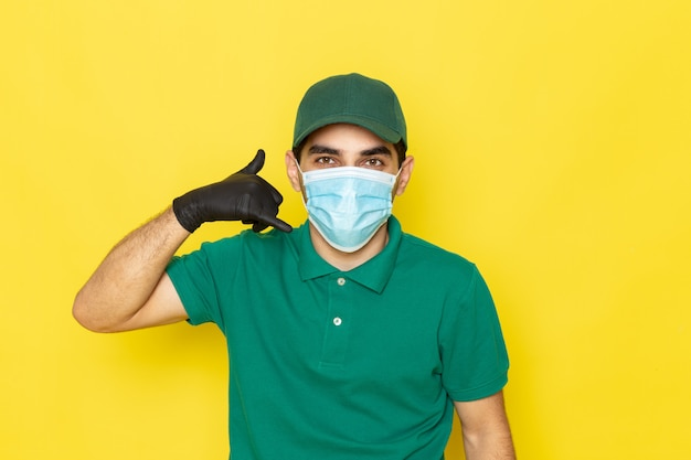 Widok z przodu młody mężczyzna kurier w zielonej koszuli, zielonej czapce, czarnych rękawiczkach, pokazujący znak połączenia telefonicznego na żółto