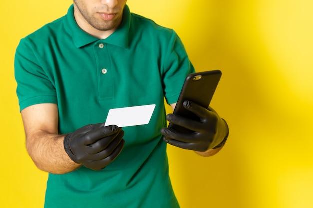 Widok z przodu młody mężczyzna kurier w zielonej koszuli zielonej czapce, trzymając białą kartę za pomocą smartfona na żółto