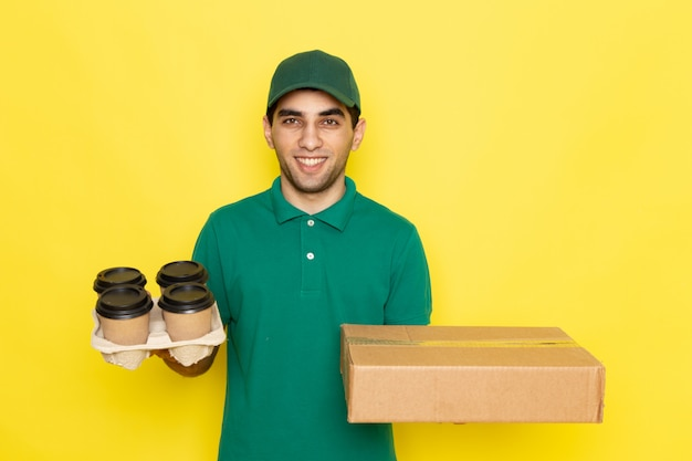 Widok z przodu młody mężczyzna kurier w zielonej koszuli zielonej czapce, trzymając pudełko dostawy i filiżanki kawy na żółto