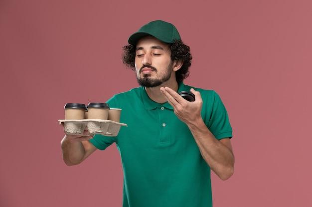 Widok z przodu młody mężczyzna kurier w zielonym mundurze i pelerynie, trzymając brązowy dostawy filiżanek kawy pachną na różowym tle mundur służbowy pracownik dostawy