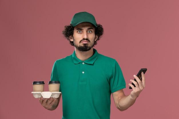 Widok z przodu młody mężczyzna kurier w zielonym mundurze i pelerynie trzymający dostawcze filiżanki kawy i jego telefon myśli na różowym tle usługa mundur pracy