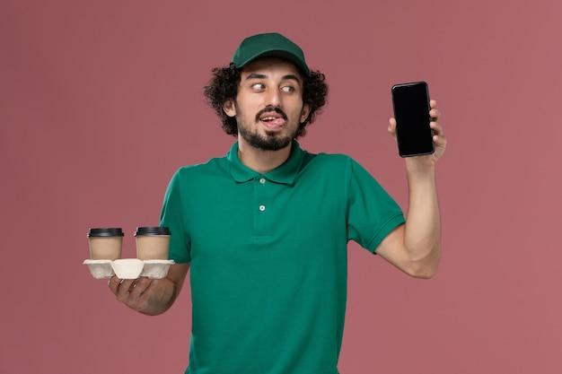 Widok z przodu młody mężczyzna kurier w zielonym mundurze i pelerynie trzymający dostawcze filiżanki kawy i jego telefon na różowym tle serwis mundurowy pracownik dostawy