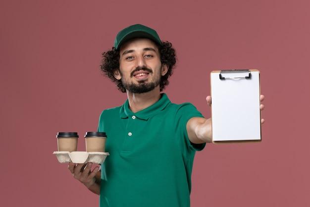 Widok z przodu młody mężczyzna kurier w zielonym mundurze i pelerynie trzymający dostawcze filiżanki kawy i notatnik na jasnoróżowym tle usługa mundur służbowy dostawa