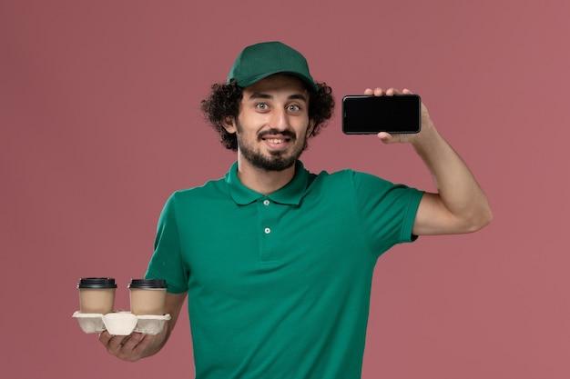 Widok z przodu młody mężczyzna kurier w zielonym mundurze i pelerynie trzymający dostawcze filiżanki kawy i telefon na jasnoróżowym biurku mundurowy pracownik dostawy