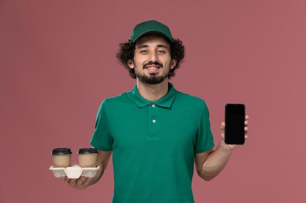 Widok z przodu młody mężczyzna kurier w zielonym mundurze i pelerynie trzymający dostawcze filiżanki kawy i telefon na jasnoróżowym tle usługa mundur służbowy dostawa