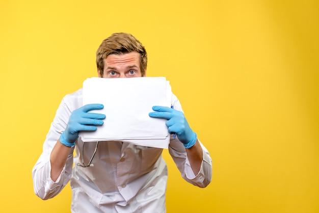 Widok z przodu młody mężczyzna lekarz posiadający analizy na żółtym tle lekarze szpitala