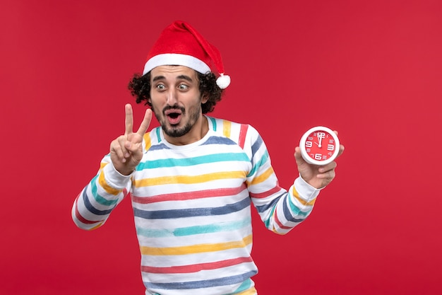 Widok Z Przodu Młody Mężczyzna Liczący Pokazujący Numer Na Czerwonej ścianie Czerwony Czas święto Nowego Roku Darmowe Zdjęcia