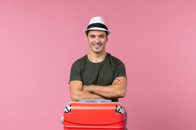 Widok z przodu młody mężczyzna na wakacjach w kapeluszu uśmiechający się na różowej przestrzeni