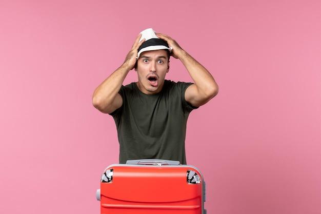 Widok z przodu młody mężczyzna na wakacjach w kapeluszu zdezorientowany na różowej przestrzeni