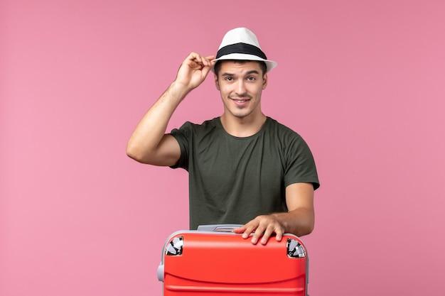 Widok z przodu młody mężczyzna na wakacjach z czerwoną torbą na różowej przestrzeni