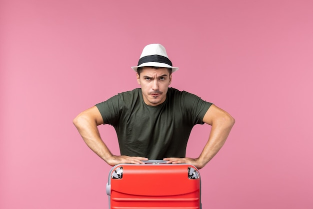 Widok z przodu młody mężczyzna na wakacjach ze swoją czerwoną torbą na różowej przestrzeni