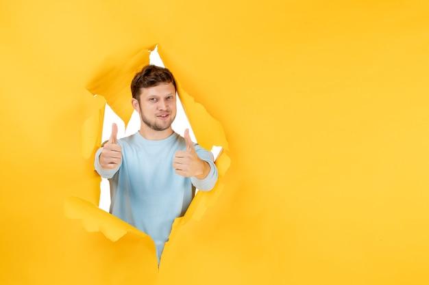 Widok z przodu młody mężczyzna na żółtej rozdartej ścianie