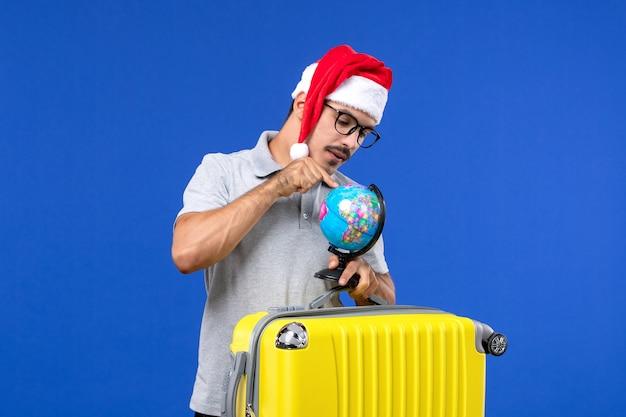 Widok z przodu młody mężczyzna niosący żółtą torbę z kulą ziemską na wycieczce wakacyjnej samolotem z niebieską ścianą