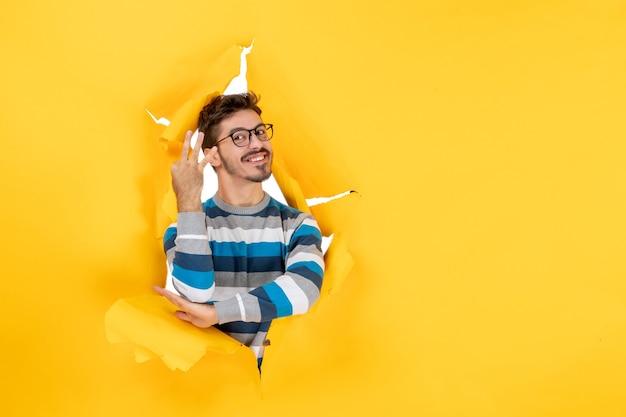 Widok z przodu młody mężczyzna pokazujący trzy palce patrzący z okrągłej dziury w żółtym kartonie