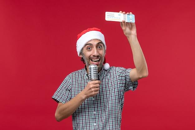 Widok z przodu młody mężczyzna posiadający bilet i mikrofon na czerwonym tle