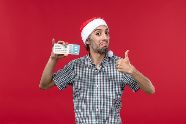 Widok z przodu młody mężczyzna posiadający bilet lotniczy na czerwonym tle