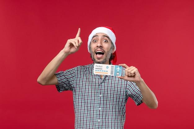 Widok z przodu młody mężczyzna posiadający bilet lotniczy na jasnoczerwonym tle
