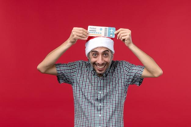 Widok z przodu młody mężczyzna posiadający bilet na czerwonym tle