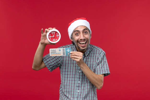 Widok z przodu młody mężczyzna posiadający bilet z zegarem na czerwonym tle