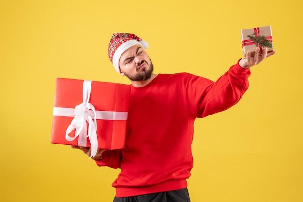 Widok z przodu młody mężczyzna posiadający boże narodzenie prezenty na żółtym tle