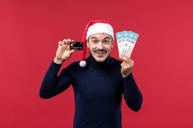 Widok z przodu młody mężczyzna posiadający karty bankowe bilety na czerwonym tle