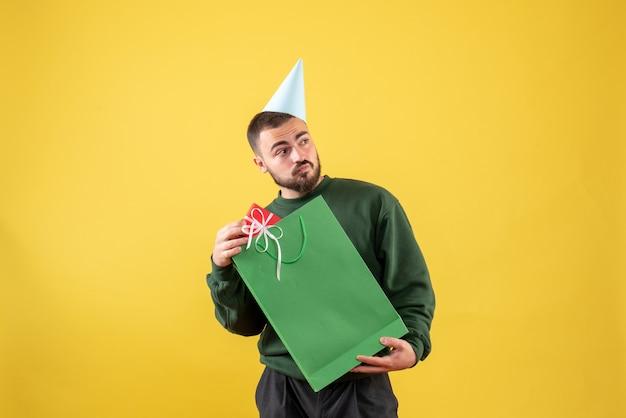 Widok z przodu młody mężczyzna posiadający mały prezent na żółtym tle